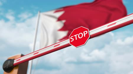 immigratie : Open boom gate on the Bahraini flag background. Free entry or lifting a ban in Bahrain
