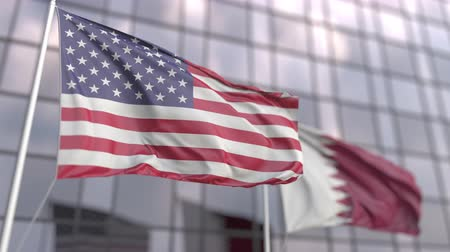 ассоциация : Waving flags of the United States and Qatar in front of a skyscraper facade