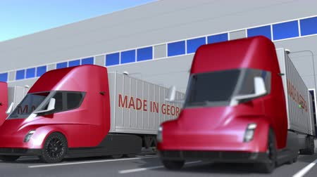 georgien : Trailer trucks with MADE IN GEORGIA text being loaded or unloaded at warehouse. Georgian business related loopable 3D animation Videos