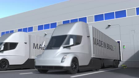 brezilya : Modern semi-trailer trucks with MADE IN BRAZIL text being loaded or unloaded at warehouse. Brazilian business related loopable 3D animation Stok Video
