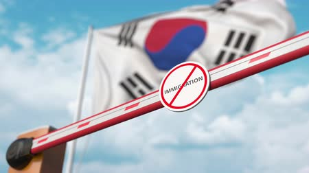 göçmen : Open boom gate with no immigration sign on the Korean flag background. Immigration welcome center in South Korea