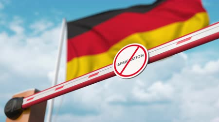 siyasi : Opening boom barrier with stop immigration sign against the German flag, immigration approval in Germany Stok Video