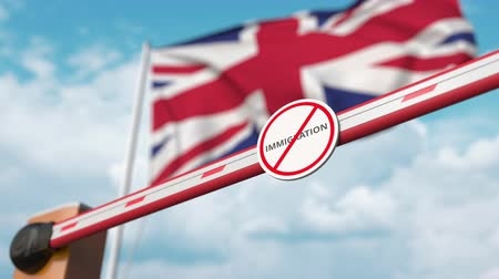 siyasi : Barrier gate with no immigration sign being opened with flag of the UK as a background. British immigration approval Stok Video