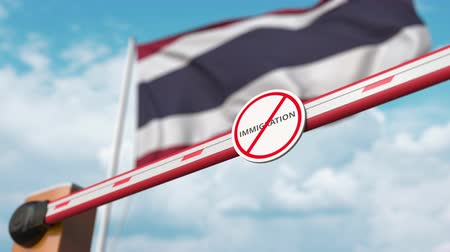 göçmen : Opening boom barrier with stop immigration sign against the Thai flag, immigration welcome center in Thailand Stok Video