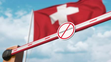 siyasi : Opening boom barrier with stop immigration sign against the Swiss flag, immigration welcome center in Switzerland