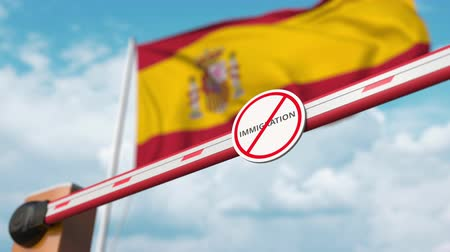 göçmen : Barrier gate with no immigration sign being opened with flag of Spain as a background. Spanish immigration welcome center