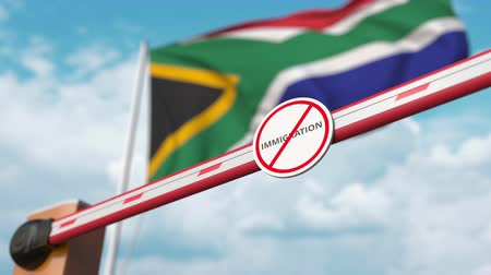siyasi : Barrier gate with no immigration sign being opened with flag of South Africa as a background. South African immigration welcome center