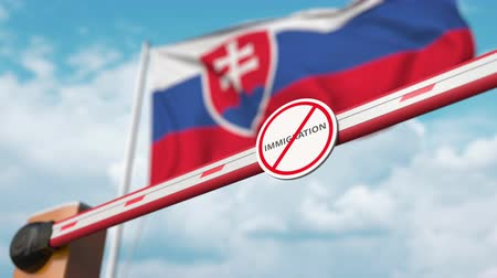 göçmen : Opening boom barrier with stop immigration sign against the Slovak flag, immigration welcome center in Slovakia