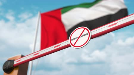 siyasi : Opening boom barrier with stop immigration sign against the UAE flag, immigration welcome center in