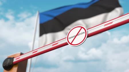 siyasi : Opening boom barrier with stop immigration sign against the Estonian flag, immigration approval in Estonia Stok Video