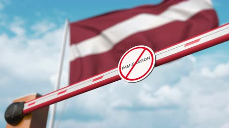 siyasi : Barrier gate with no immigration sign being opened with flag of Latvia as a background. Latvian immigration welcome center