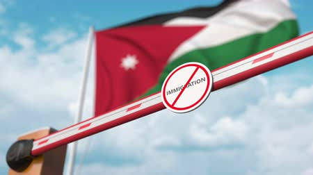 siyasi : Barrier gate with no immigration sign being opened with flag of Jordan as a background. Jordanian immigration welcome center