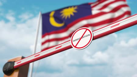 göçmen : Barrier gate with no immigration sign being opened with flag of Malaysia as a background. Malaysian immigration welcome center