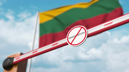 siyasi : Opening boom barrier with stop immigration sign against the Lithuanian flag, immigration welcome center in Lithuania