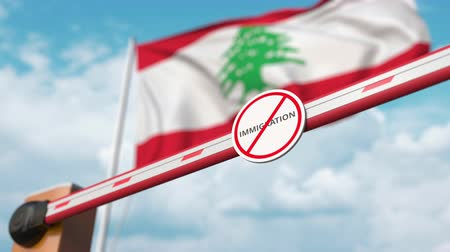 siyasi : Opening boom barrier with stop immigration sign against the Lebanonese flag, immigration welcome center in Lebanon