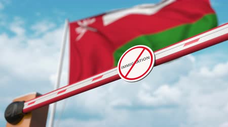 siyasi : Opening boom barrier with stop immigration sign against the Omani flag, immigration approval in Oman