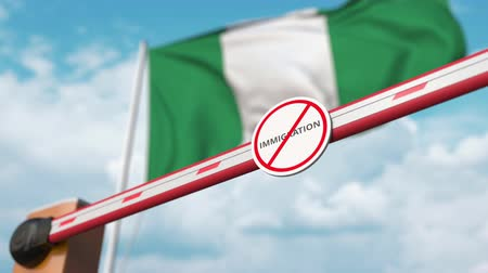 siyasi : Opening boom barrier with stop immigration sign against the Nigerian flag, immigration welcome center in Nigeria