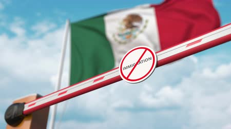 siyasi : Opening boom barrier with stop immigration sign against the Mexican flag, immigration welcome center in Mexico