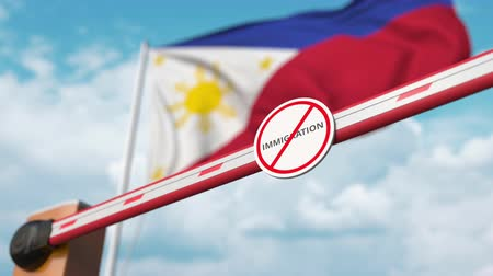 siyasi : Barrier gate with no immigration sign being opened with flag of the Philippines as a background. Immigration approval