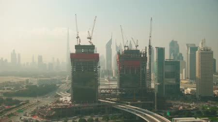 fejleszt : DUBAI, UNITED ARAB EMIRATES - DECEMBER 26, 2019. Aerial dolly zoom shot of the skyline behind skyscrapers construction site