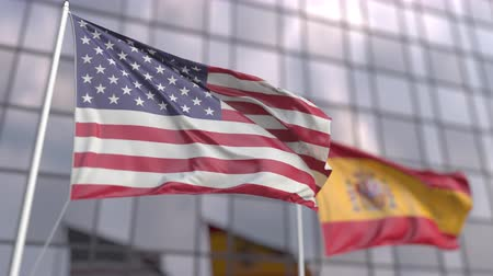 ассоциация : Waving flags of the USA and Spain in front of a modern skyscraper facade