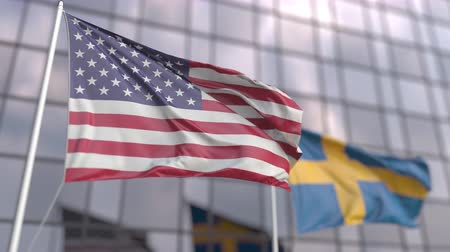 siyasi : Waving flags of the USA and Sweden in front of a modern skyscraper Stok Video