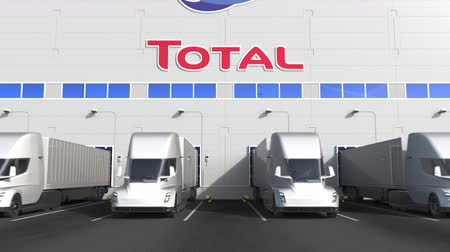 celkový : Electric semi-trailer trucks at warehouse loading bay with TOTAL S.A. logo on the wall. Editorial 3D animation