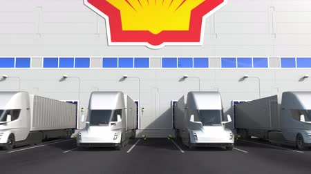 unload : Electric trailer trucks at warehouse loading bay with ROYAL DUTCH SHELL logo on the wall. Editorial 3D animation Stock Footage