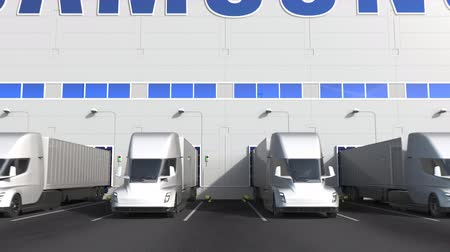 unload : Electric trailer trucks at warehouse loading bay with SAMSUNG logo on the wall. Editorial 3D animation