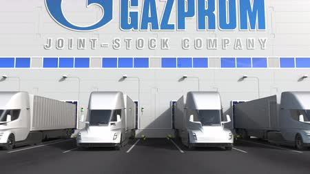 gazprom : Electric semi-trailer trucks at warehouse loading bay with Gazprom logo on the wall. Editorial 3D animation