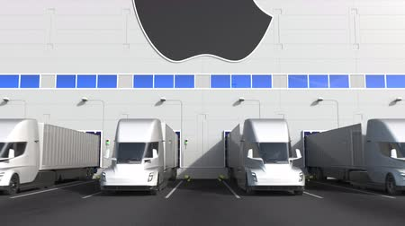unload : Electric semi-trailer trucks at warehouse loading bay with APPLE INC logo on the wall. Editorial 3D animation
