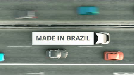 brasileiro : Aerial top down view of semi-trailer trucks with MADE IN BRAZIL text driving along the highway. Brazilian business related loopable 3D animation Stock Footage