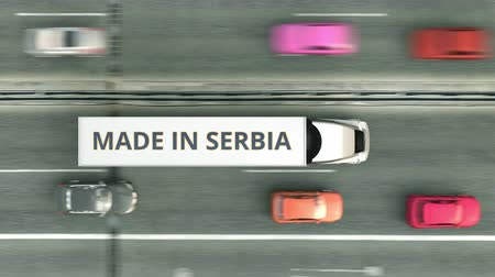 sérvia : Aerial overhead view of trailer trucks with MADE IN SERBIA text driving along the highway. Serbian business related loopable 3D animation