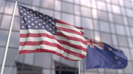 siyasi : Waving flags of the USA and New Zealand in front of a modern skyscraper