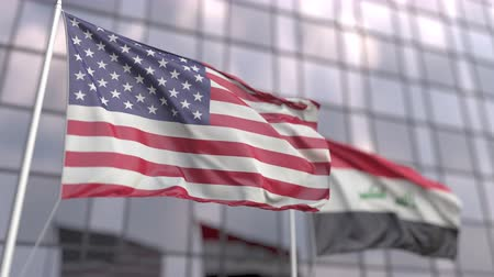 siyasi : Waving flags of the United States and Iraq in front of a modern skyscraper