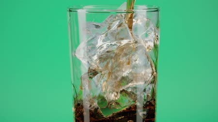 кубик льда : Pouring cola into a glass with ice cubes against green background, close-up shot on Red