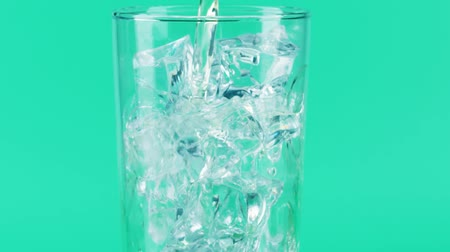 кубик льда : Pouring lemonade into a glass with ice cubes, close-up shot on Red Стоковые видеозаписи