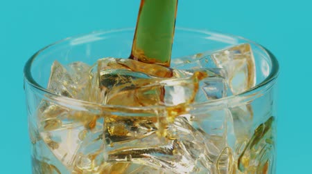 cubos de hielo : Pouring cola into a glass full of ice cubes on cyan background, slow motion macro shot on Red