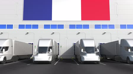 disposição : Electric semi-trailer trucks at warehouse loading dock with flag of FRANCE. French logistics related conceptual 3D animation