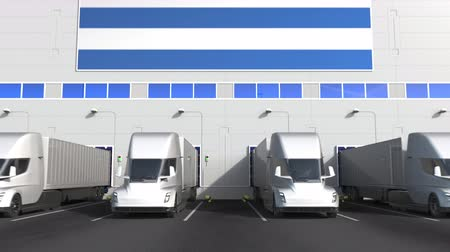 調達 : Modern trailer trucks load or unload at warehouse docks with flag of GREECE. Greek logistics related conceptual 3D animation 動画素材