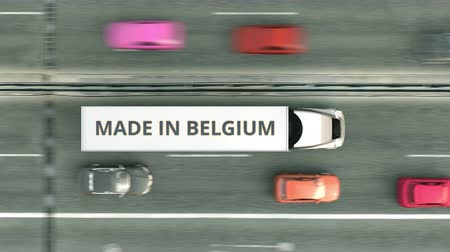 доставлять : Trailer trucks with MADE IN BELGIUM text driving along the highway. Belgian business related loopable 3D animation Стоковые видеозаписи
