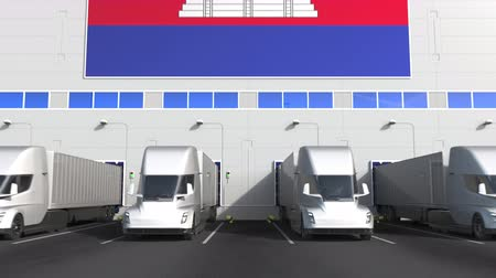 disposição : Semi-trailer trucks at warehouse loading bay with flag of CAMBODIA. Cambodian logistics related conceptual 3D animation