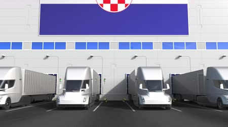 hırvatistan : Electric trucks at warehouse loading bay with flag of CROATIA. Croatian logistics related conceptual 3D animation