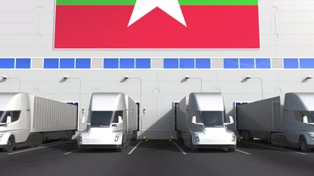 mianmar : Semi-trailer trucks at warehouse loading dock with flag of Myanmar. Myanma logistics related conceptual 3D animation Stock Footage