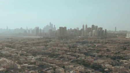 резидент : Aerial shot of skyscrapers silhouettes behind residential area in Dubai, UAE
