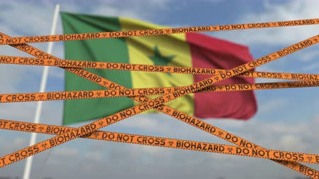 níveis : Do not cross biohazard tape lines on the Senegalese flag background. Restricted entry or quarantine in Senegal. Conceptual looping 3D animation