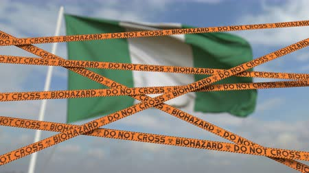 nigeria flag : Biohazard restriction tape lines against the Nigerian flag. Restricted border crossing or quarantine in Nigeria. Conceptual looping 3D animation
