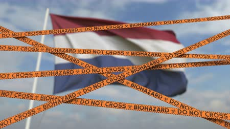 border crossing : Biohazard restriction tape lines against the Dutch flag. Restricted border crossing or quarantine in the Netherlands. Conceptual looping 3D animation Stock Footage