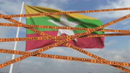 border crossing : Biohazard restriction tape lines against the Myanma flag. Restricted border crossing or quarantine in Myanmar. Conceptual looping 3D animation