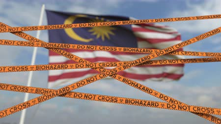 malásia : Caution biohazard tape with flag of Malaysia as a background. Malaysian restricted border crossing or quarantine. Conceptual looping 3D animation Vídeos